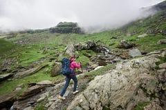 Girl hiker climbs to top of mountainous country Romania. Girl hiker climbs to the top of the mountainous country of Romania. Clouds shroud mountains. Woman with Stock Photos