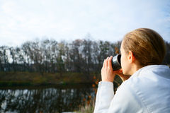 Girl hiker drinking tea from a thermos on the autumn nature Stock Photo
