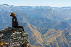 Girl hiker enjoy the view and the sun on top of the mountain Stock Image