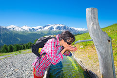 Girl hiker quenches thirst at the fountain during a mountain tre Stock Photos