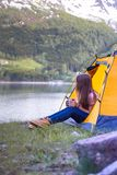 Girl hiker sits in a tent Stock Images
