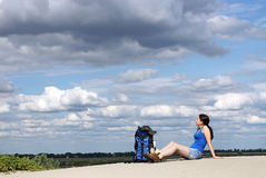 Girl hiker sitting on the sand Royalty Free Stock Photo