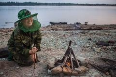 Girl hiker smiling and looking to camera around campfire on river shore at evening Royalty Free Stock Photo