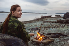 Girl hiker stirs firewood around campfire on river shore at evening Royalty Free Stock Photos