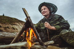 Girl hiker stirs firewood and looking afar around campfire on river shore at evening Royalty Free Stock Photography