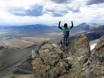 Girl hiker summit mountain top. In triumph Royalty Free Stock Image