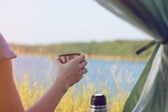 Girl hiker in a tent and holding a cup of warm tea. Mountains and lake in the background. Stock Photography