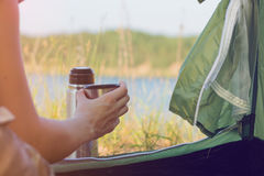 Girl hiker in a tent and holding a cup of warm tea. Mountains and lake in the background. Stock Image