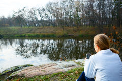 Girl hiker with thermo cup of tea in hand on the autumn nature Stock Photo