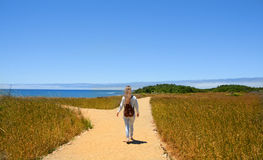 Girl hiking on the road. Girl walking on the road , at forked road making decision which way to go. Hiking trip by the Pacific ocean. Año Nuevo State Park is a Royalty Free Stock Images