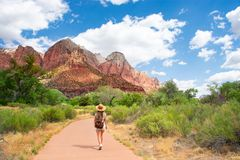 Girl on hiking trip in the red mountains, walking on pathway. stock photo