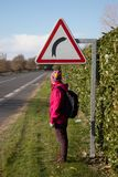 Girl hiking under a curve sign on the road stock photography