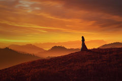 Girl on hill at sunset stock image