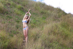 The girl on a hillock. The beautiful girl in a bathing suit on a hillock in a grass Stock Photography
