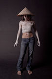 Girl in a сhinese hat. Girl in jeans, bandages, and a hat standing on a black background Royalty Free Stock Photography