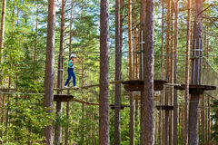 Girl on hinged trail in extreme rope Park Royalty Free Stock Images