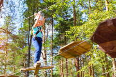Girl on hinged trail in extreme rope Park Royalty Free Stock Photos