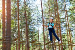 Girl on hinged trail in extreme rope Park Stock Images