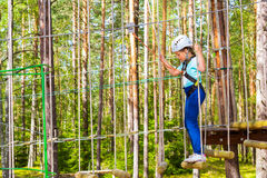 Girl on hinged trail in extreme rope Park Royalty Free Stock Photo
