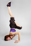Girl in hip-hop clothes making freeze. Young redhead girl in hip-hop clothes making freeze, break dance position with head over heels, full body Stock Images