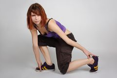 Girl in hip-hop clothes sitting on one knee Royalty Free Stock Photography