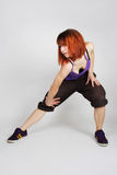 Girl in hip-hop clothes standing and bending. Young redhead girl in hip-hop clothes standing and bending at front, full body Stock Photos