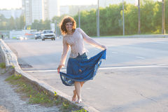 Girl, hippie, walking on side of carriageway Royalty Free Stock Photo
