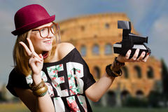 Girl in hipster glasses holding camera on Coliseum Royalty Free Stock Photo