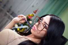 Girl in hipster glasses with pencil in christmas Stock Photos