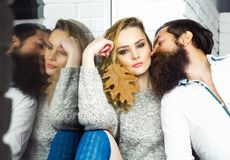 Girl and hipster reflect in window glass. Couple in love. Man with beard and women with leaf. Date, flirt, relationship, romance. Sensuality, seduction concept stock images