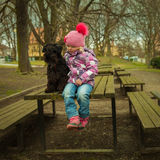 girl with his black schnauzer dog on a wooden bench stock photo
