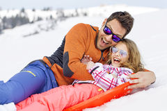 Girl and his father sledding very fast Stock Images