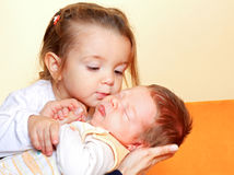 Girl with his newborn brother. Young sister kissing her newborn adorable brother Stock Image