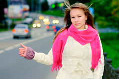 Girl hitch-hike on highway Stock Images