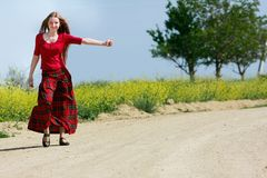 Girl hitchhiking on country road Royalty Free Stock Image