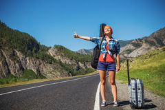 Girl hitchhiking. Girl with a guitar and a suitcase hitchhiking on a mountain road Stock Photos