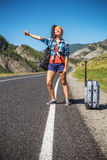 Girl hitchhiking. Girl with a guitar and a suitcase hitchhiking on a mountain road Stock Images