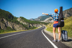 Girl hitchhiking. Girl with a guitar and a suitcase hitchhiking on a mountain road Royalty Free Stock Image