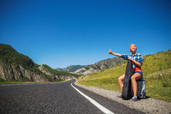 Girl hitchhiking. Girl with a guitar and a suitcase hitchhiking on a mountain road Stock Image