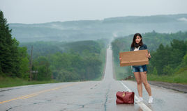 Girl hitchhiking holds up a  sign Stock Images