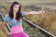 Girl hitchhiking at railroad Royalty Free Stock Photos