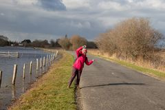 Girl hitchhiking on a rural road wearing a pink c stock photo