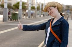 Girl hitchhiking on the street Stock Photo