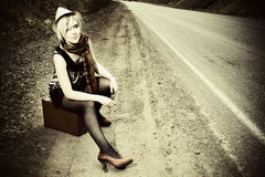 Girl hitchhiking with suitcase Royalty Free Stock Images