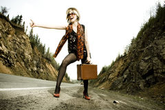 Girl hitchhiking with suitcase Stock Photography
