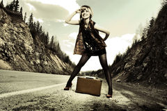 Girl hitchhiking with suitcase Royalty Free Stock Image