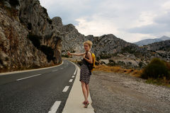 Girl hitchhiking with thumb up Royalty Free Stock Photography