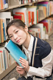 Girl hold a book against her face Stock Image