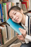 Girl hold a book against her face Stock Photo