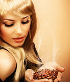 Girl hold coffee beans. Closeup portrait of pretty blonde girl hold hot roasted coffee beans in hands isolated on brown background, picture of cute woman Royalty Free Stock Photos